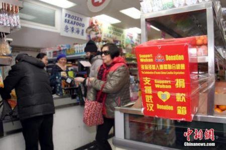 当地时间2月23日,顾客在加拿大多伦多唐人街一间华人超市购物时,从当地侨团为支援中国内地抗击疫情而在店内设置的捐款箱旁走过。超市负责人表示,新型冠状病毒疫情发生以来,华人商区生意受到明显冲击,随着商家、政府等多方努力、宣传,消减民众恐慌情绪,目前超市生意逐渐有所好转。中新社记者 余瑞冬 摄