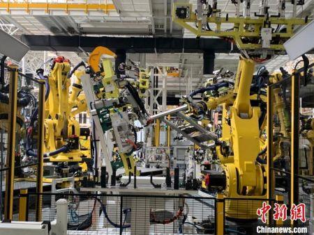 """16日,在位于江西上饶的一家新能源电动汽车公司的智慧工厂内,412台宛如""""变形金刚""""的机器人正同时作业。 李韵涵 摄"""