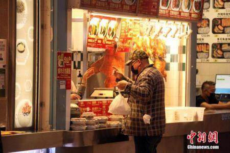"""资料图:当地时间12月14日,加拿大大多伦多地区万锦市(Markham)一商场内,顾客在一家港式烧腊食档购买打包餐食。自该日起,包括万锦市等华人聚居区所在的约克区被划入安大略省防疫级别最高的""""灰色地区"""",实施至少为期四周的封禁。因应目前仍然严峻的疫情,加拿大多地正继续强化防疫限制措施。 中新社记者 余瑞冬 摄"""