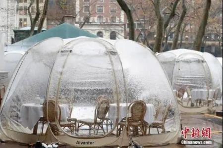 """资料图:2020年12月9日,美国纽约迎来今冬首场降雪,布莱恩公园的户外用餐""""泡泡屋""""覆盖白雪。中新社记者 廖攀 摄"""