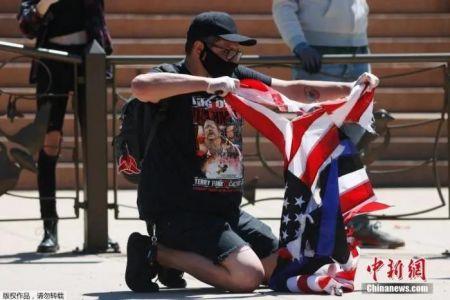 资料图:当地时间2020年5月29日,美国丹佛,示威者撕毁了一面美国国旗。