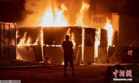 资料图:弗洛伊德之死引发了大规模抗议,有暴徒趁机纵火和抢劫。图为抗议者在明尼阿波利斯市第三警察局附近烧毁一处建筑设施。