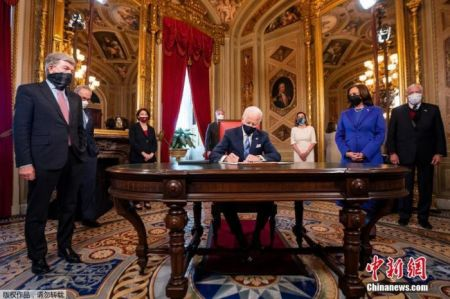 图为美国总统拜登在华盛顿白宫椭圆形办公室签署行政命令。