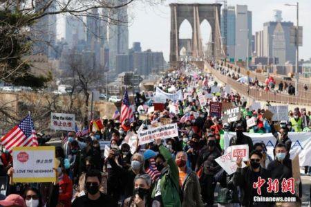 当地时间4月4日,纽约举行反仇恨亚裔大游行,上万民众手持标语在曼哈顿弗利广场集会后,游行穿过布鲁克林大桥至布鲁克林卡德曼广场。图为民众游行穿过布鲁克林大桥。 中新社记者 廖攀 摄